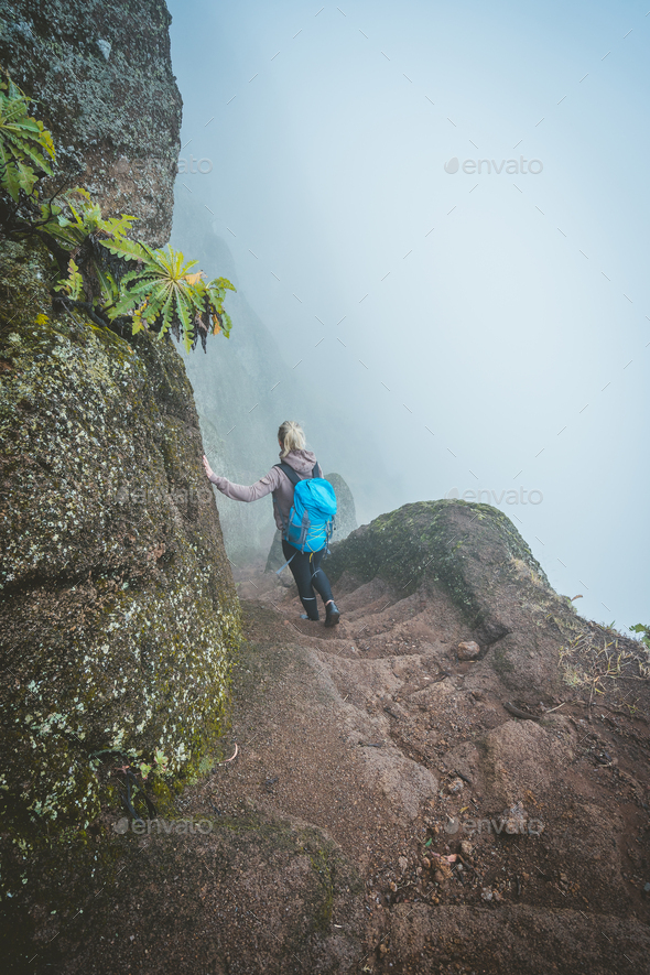 Hiker women with backpack walking down the steep slope of the rock in the foggy mountains - Stock Photo - Images