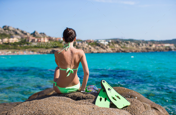 Young woman with snorkeling equipment on big stones - Stock Photo - Images