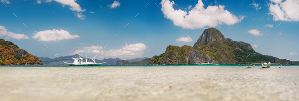 Cadlao island background with filippino traditional boats in shallow bay at El Nido bay from low - Stock Photo - Images