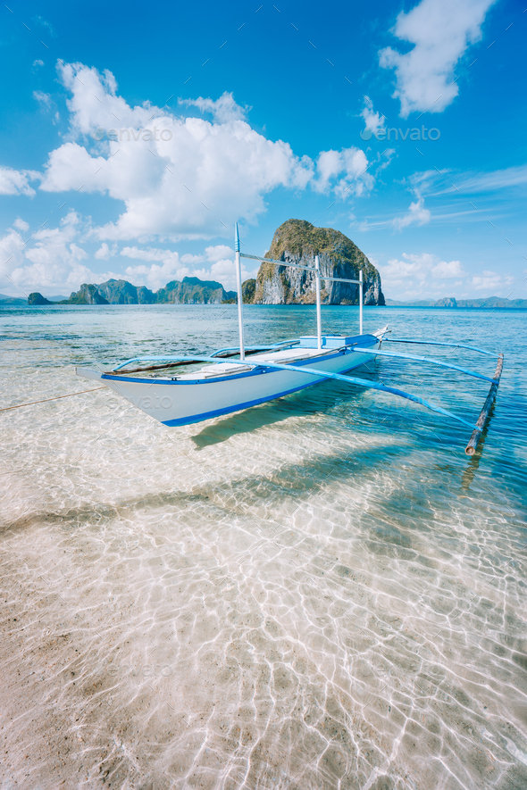 El Nido, Palawan, Philippines. Banca boat on sandy beach in shallow crystal clear water on island - Stock Photo - Images