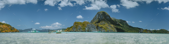 Low angle view of traditional filippino boats in El Nido bay in front of epic Cadlao island. Palawan - Stock Photo - Images