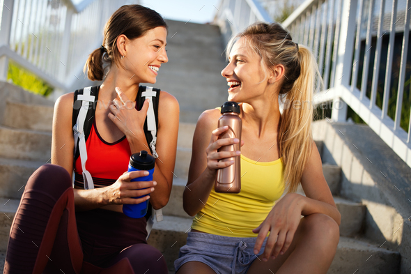 Happy fit friends women drinking water after running outdoor - Stock Photo - Images
