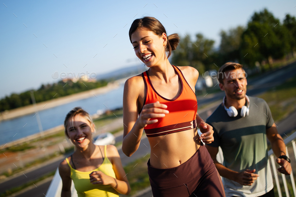 Fitness, sport, people and running concept. Happy fit friends running outdoors - Stock Photo - Images