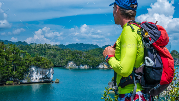 Traveler with Backpack enjoy the View over Roks in Kabui Bay near Waigeo. West Papuan, Raja Ampat - Stock Photo - Images