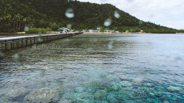 Wooden jetty near Yenbuba village leading to Mansuar island in Raja Ampat. Beautiful corals in - Stock Photo - Images