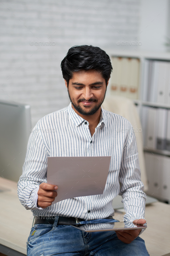 Businessman reading document - Stock Photo - Images