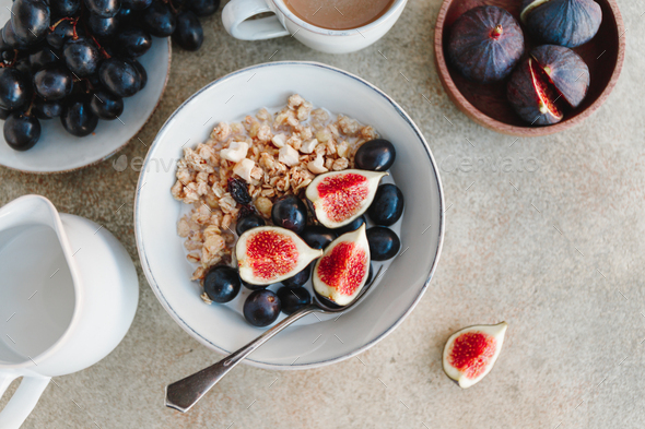 Top view of a breakfast bowl with granola, blue grape and fig slices - Stock Photo - Images