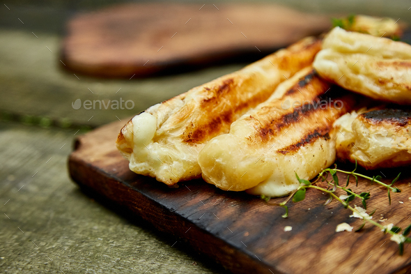 Grilled cheese puff pastry on the wooden cutting board. - Stock Photo - Images