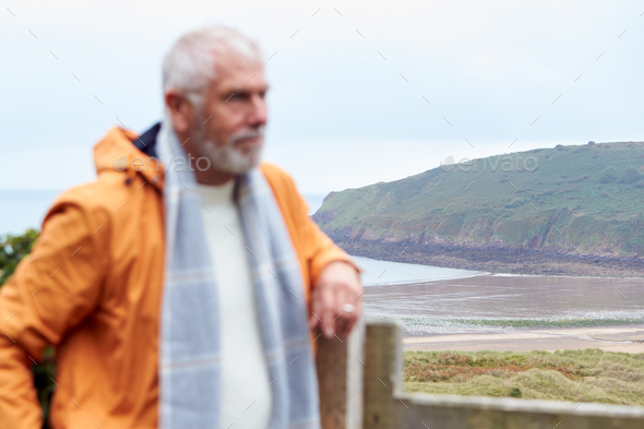 Defocused Shot Of Active Senior Man Walking Along Coastal Path In Fall Or Winter By Gate - Stock Photo - Images