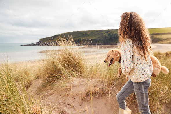 Girl Carrying Pet Dog Exploring Sand Dunes On Winter Beach Vacation - Stock Photo - Images