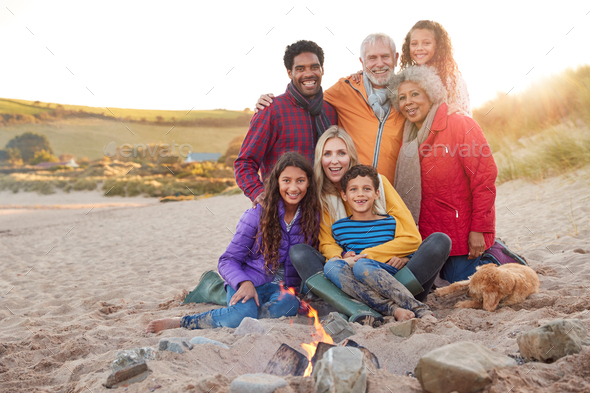 Portrait Of Active Multi-Generation Family With Pet Dog Sitting By Fire On Winter Beach Vacation - Stock Photo - Images
