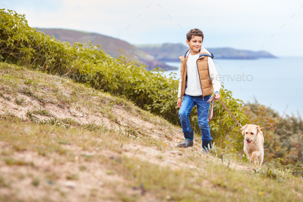 Boy Exercising Dog On Leash Walking Up Hill By Sea - Stock Photo - Images
