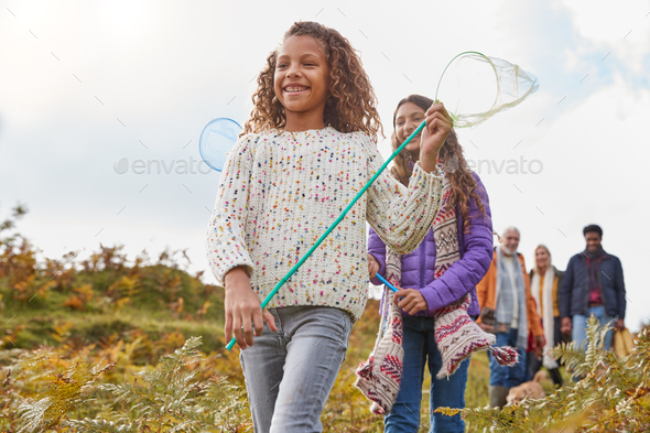 Multi-Generation Family Walking Through Countryside Carrying Fishing Nets On Winter Beach Vacation - Stock Photo - Images