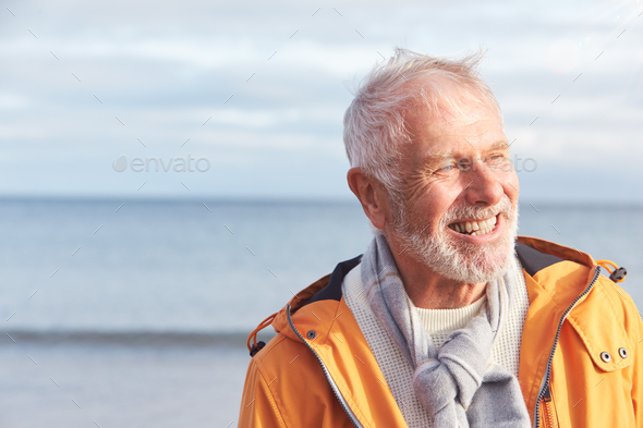 Head And Shoulders Shot Of Active Senior Man Walking Along Winter Beach With Sea Behind - Stock Photo - Images