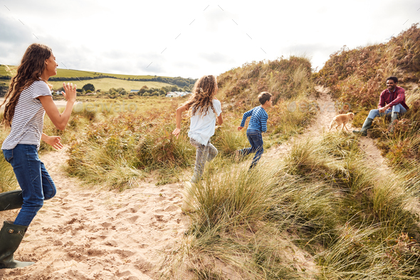 Three Children Having Fun Exploring In Sand Dunes On Winter Beach Vacation Run To Father - Stock Photo - Images