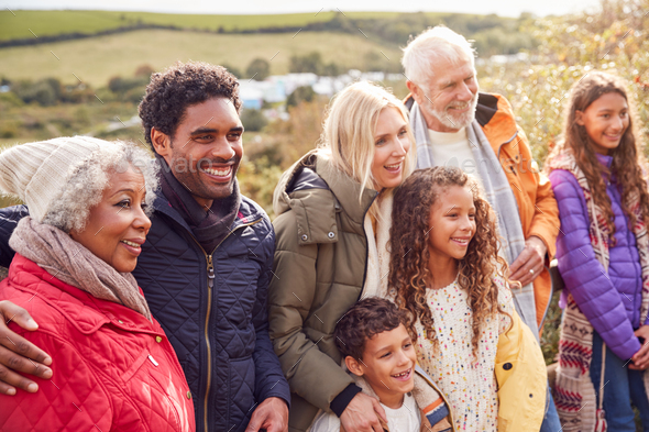 Portrait Of Active Multi-Generation Family On Winter Beach Vacation Resting By Gate - Stock Photo - Images