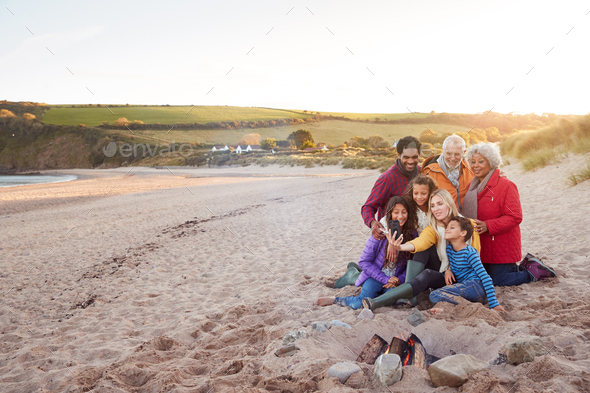 Wide Angle Shot Of Multi-Generation Family Sitting By Fire On Winter Beach Vacation Taking Selfie - Stock Photo - Images