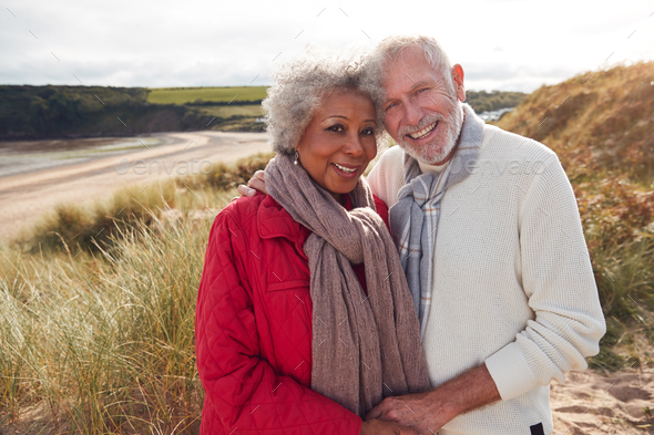 Portrait of Loving Senior Couple Standing And Hugging On Walk In Sand Dunes On Winter Beach Vacation - Stock Photo - Images