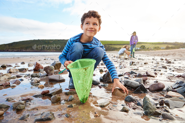 Children Looking In Rockpools On Winter Beach Vacation - Stock Photo - Images
