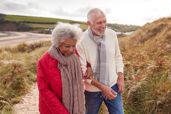 Loving Active Senior Couple Walking Arm In Arm Through Sand Dunes On Winter Beach Vacation - Stock Photo - Images