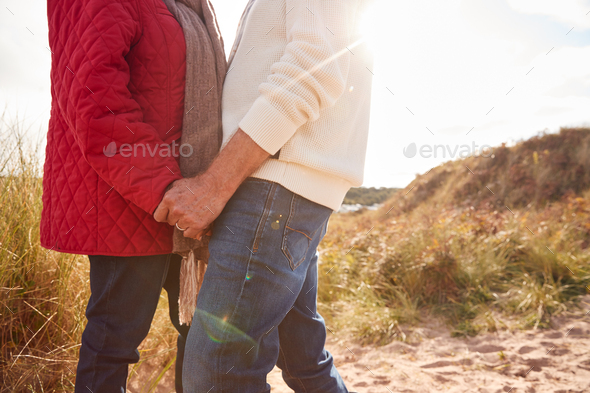 Close Up Of Loving Senior Couple Holding Hands Walking Through Sand Dunes On Winter Vacation - Stock Photo - Images