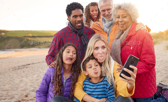 Multi-Generation Family Sitting By Fire On Winter Beach Vacation Taking Selfie - Stock Photo - Images