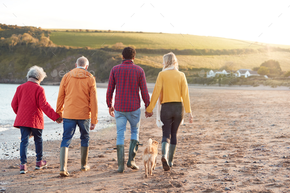 Senior Couple Hold Hands As They Walk Along Shoreline With Adult Offspring On Winter Beach Vacation - Stock Photo - Images