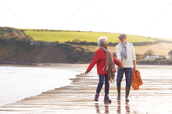 Senior Couple Hold Hands As They Walk Along Shoreline On Winter Beach Vacation - Stock Photo - Images