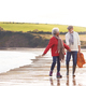 Senior Couple Hold Hands As They Walk Along Shoreline On Winter Beach Vacation - PhotoDune Item for Sale