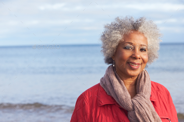 Head And Shoulders Portrait Of Active Senior Woman Walking Along Winter Beach With Sea Behind - Stock Photo - Images