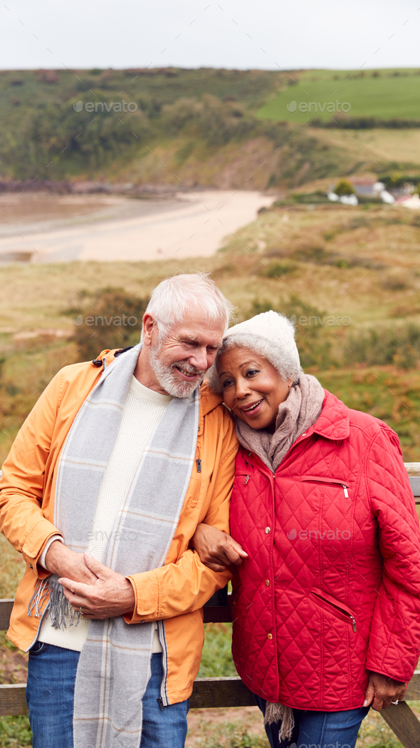 Loving Active Senior Couple Resting By Gate As They Walk Along Coastal Path In Winter - Stock Photo - Images
