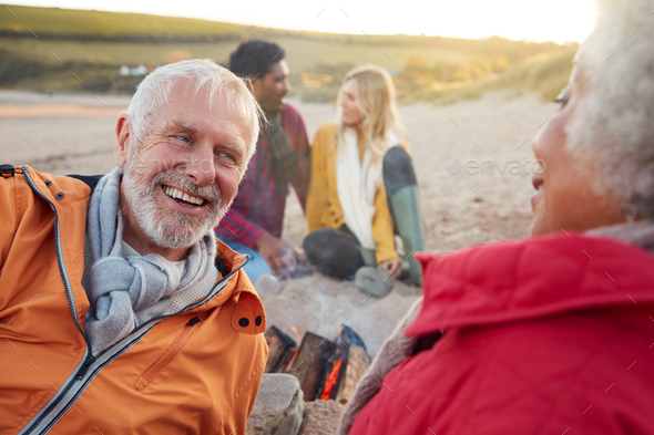 Loving Senior Couple Relaxing By Fire With Adult Offspring On Winter Beach Vacation - Stock Photo - Images