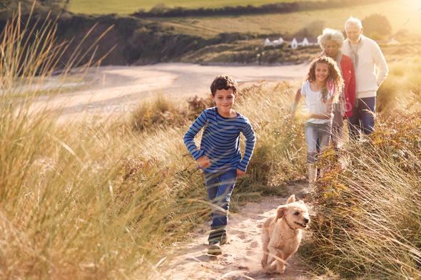 Grandchildren And Pet Dog Exploring Sand Dunes With Grandparents On Winter Beach Vacation - Stock Photo - Images
