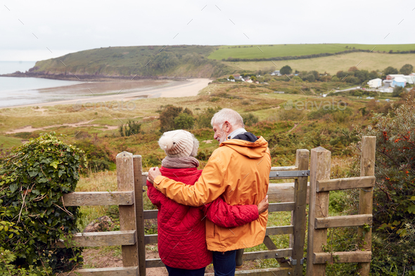Rear View Of Active Senior Couple Looking Out Over Gate As They Walk Along Coastal Path In Fall - Stock Photo - Images