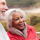 Close Up Of Loving Active Senior Couple Resting By Gate As They Walk Along Coastal Path In Winter - PhotoDune Item for Sale
