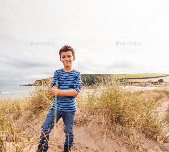 Portrait Of Boy Exploring Sand Dunes On Winter Beach Vacation - Stock Photo - Images