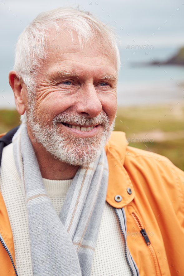 Active Senior Man Walking Along Coastal Path In Fall Or Winter By Gate With Beach And Cliffs Behind - Stock Photo - Images