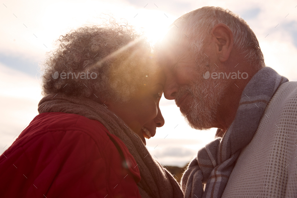 Head To Head Shot Of Loving Senior Couple Walking Outdoors Against Flaring Sun - Stock Photo - Images