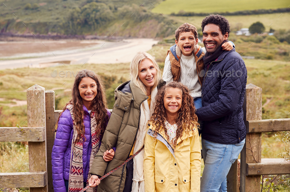 Portrait Of Active Multi-Cultural Family Standing By Gate On Winter Beach Vacation - Stock Photo - Images