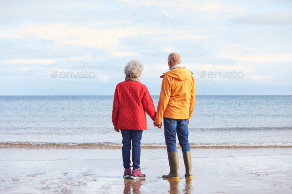 Rear View Of Senior Couple Holding Hands Looking Out To Sea On Winter Beach Vacation - Stock Photo - Images