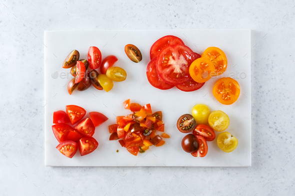 Red and yellow cherry tomatoes on the white marble board - Stock Photo - Images
