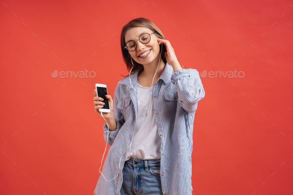 Smiling girl in casual clothes and earphones dancing moving hands. - Stock Photo - Images