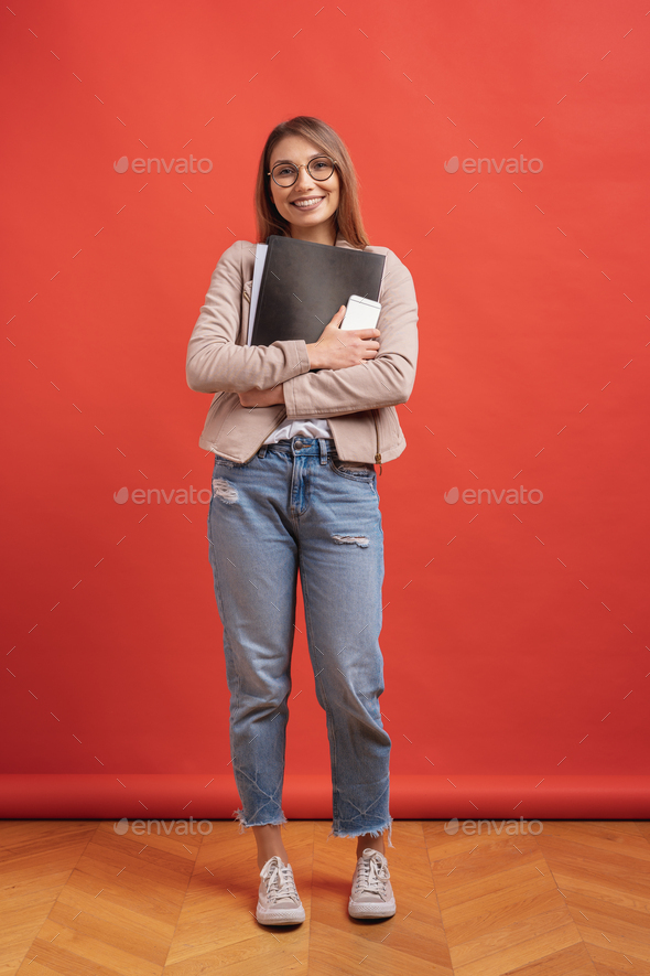 Young smiling student or intern in eyeglasses standing with a folder on red background. - Stock Photo - Images