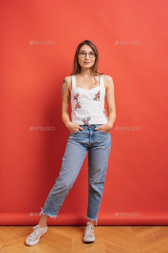 Pretty female model posing with a smiling face expression on red background - Stock Photo - Images