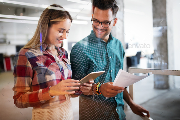 Colleagues discussing business and smiling while walking through the office corridor - Stock Photo - Images