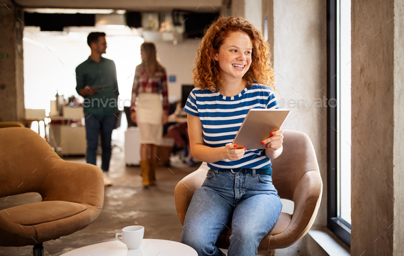 Portrait of a smiling designer, student, freelancer business woman using tablet computer - Stock Photo - Images