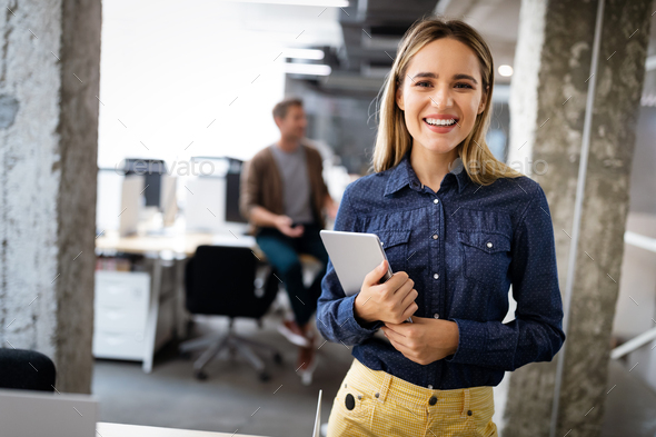 Beautiful business woman holding tablet computer in office - Stock Photo - Images