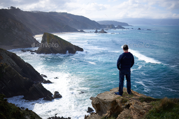 One man enjoying the view of the cliffs of Loiba, Galicia - Stock Photo - Images