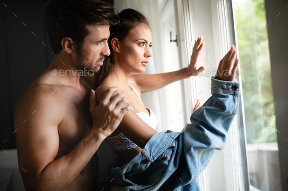 Beautiful woman and handsome muscular man close to each other in erotic pose - Stock Photo - Images