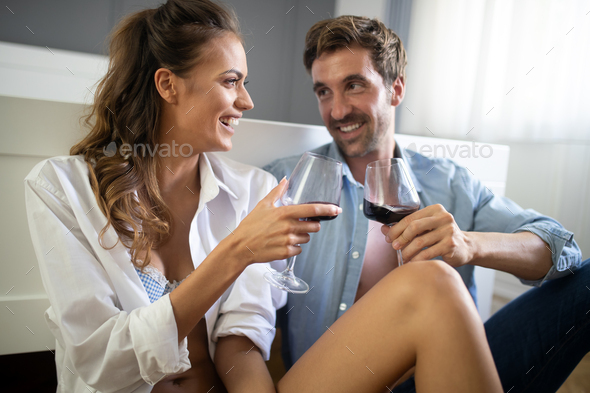 Beautiful couple is smiling and hugging while spending time together in bedroom - Stock Photo - Images